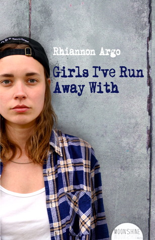A girl with a backwards hat and blue plaid stares at the camera