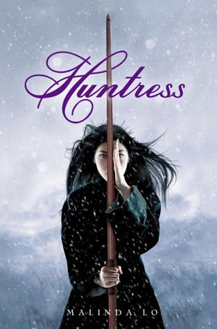 A girl in black holds a wooden lance in the a snowy landscape