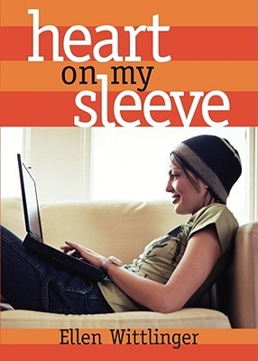 A girl in a beanie sitting on a tan couch looking at a laptop