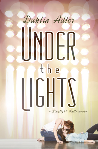 Most of the cover is lights as if one a stage or a theater. At the bottom of the cover are two white girls, one laying with her head in the others lap and their faces very close together but not quite touching.