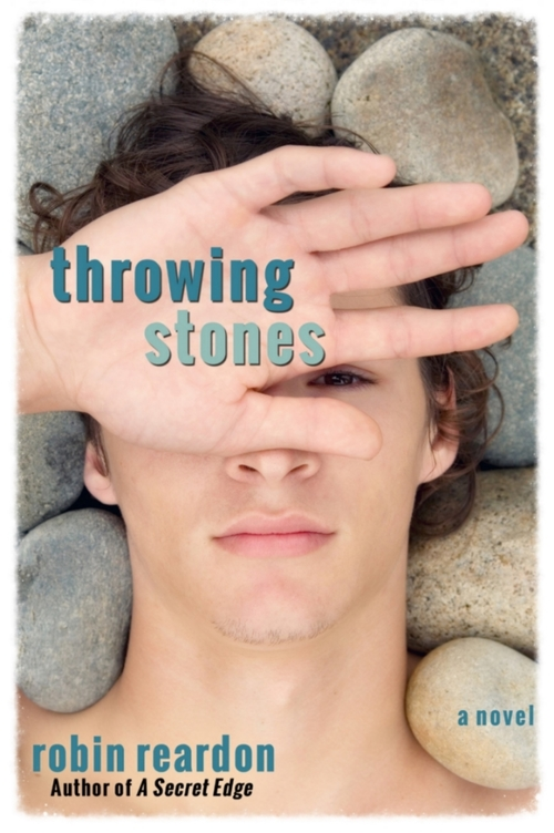 A boy with white skin lies on the rocks with his hand over his face, palm up.  Through his fingers you can see one eye.