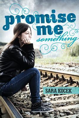 A girl sits on some train tracks