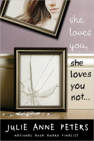 A shattered picture frame sits beneath another frame of a girl, tilted