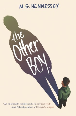 A boy with short hair stands facing away in a green hoodie with his hands in his pockets.  He stares at his shadow which takes up most of the cover and is about three times his size.