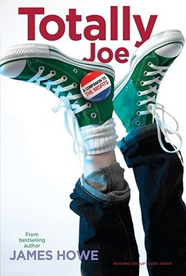 A pair of legs with green converses with a button stuck to them colored red white and blue