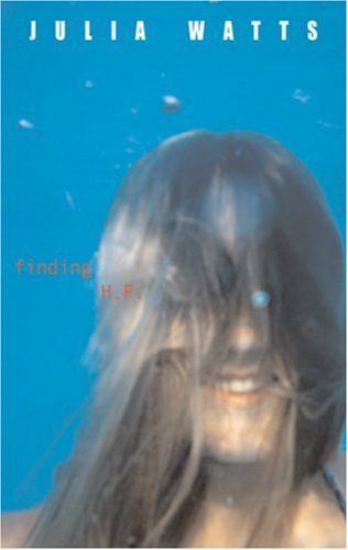 A blurry image of a girl underwater, her hair in her face, and she's smiling