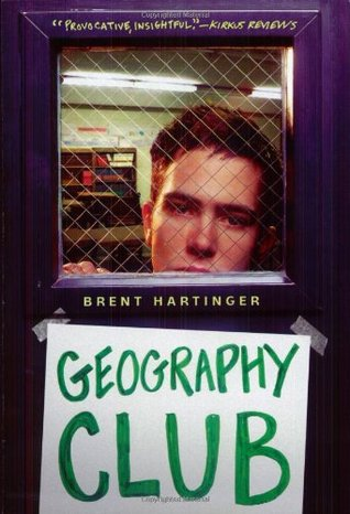 """A boy looks through a door with a sign that reads """"geography club"""" taped on the outside."""